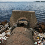 RIO DE JANEIRO, BRAZIL - MAY 09:  An abandoned drainage pipe sits on the edge of polluted Guanabara Bay, on May 9, 2014 in Rio de Janeiro, Brazil. The city is taking on a number of infrastructure projects and cleaning up Guanabara Bay, site of Olympic sailing events, in time for the Rio 2016 Olympic Games.  (Photo by Mario Tama/Getty Images)