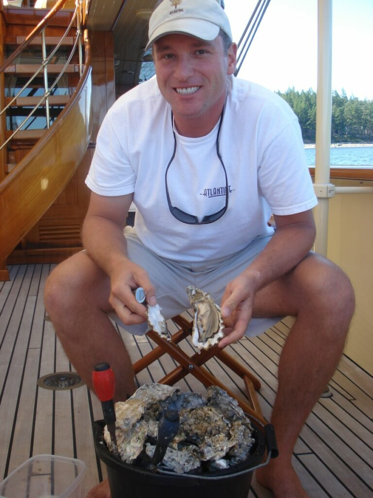 Captain Justin Christo on Atlantide Shucking oysters