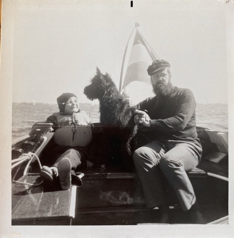 Rom as a child on a boat with his dad and their dog